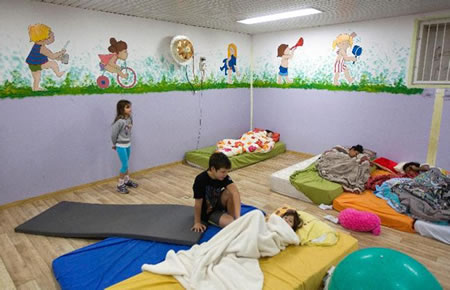 Israeli children wake up in the morning inside a bomb shelter at Kibbutz Reim, outside the central Gaza Strip November 18, 2012. Israel bombed Palestinian militant targets in the Gaza Strip from air and sea for a fifth straight day on Sunday, preparing for a possible ground invasion while also spelling out its conditions for a truce. Palestinian fire into Israel subsided during the night but resumed in the morning, with two rockets targeting Tel Aviv. REUTERS/Ronen Zvulun (ISRAEL - Tags: CIVIL UNREST POLITICS CONFLICT) CREDIT: REUTERS