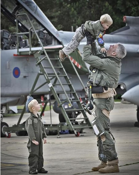 WG CDR Turk and his children...part of the winning entry from RAF Marham Category A 'Photographic Section Portfolio' sponsored by Canaon UK. 'Welcome Home' by SAC Chris Hill. IMAGE OF OC 9 SQN, WG CDR TURK, LIFTING HIS CHILD IN THE AIR WHILST HIS OTHER CHILD LOOKS UP WAITING FOR HIS TURN. TAKEN ON 9 SQN'S TORNADO'S RETURN TO RAF MARHAM FROM OPERATION ELLAMY.